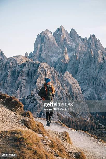 Female hiker follows trail in mountains, autumn