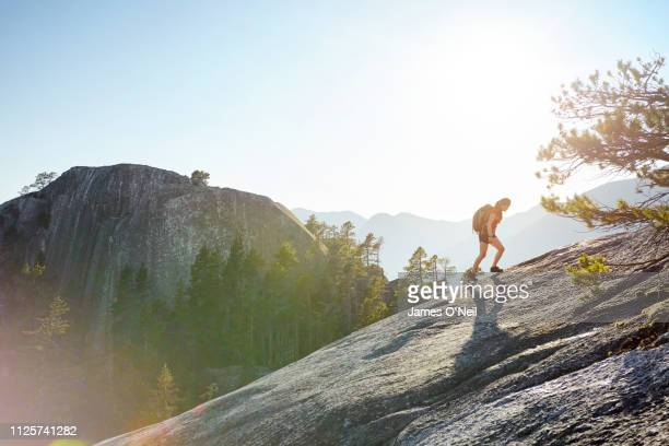 female hiker going uphill with distant peaks - uphill stock pictures, royalty-free photos & images