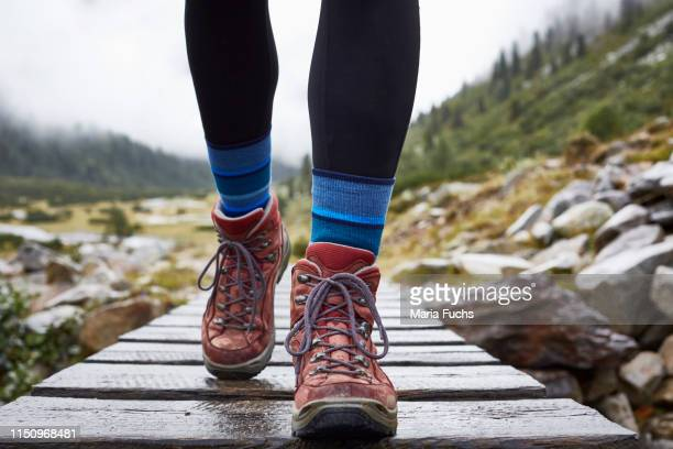 female hiker hiking across wooden footbridge, cropped view of legs and hiking boots - hiking boot stock pictures, royalty-free photos & images