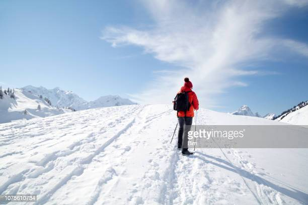 female hiker in snowy mountain - red coat stock pictures, royalty-free photos & images