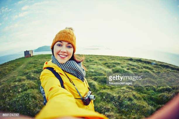 Female hiker in warm clothing taking selfie on grassy mountain