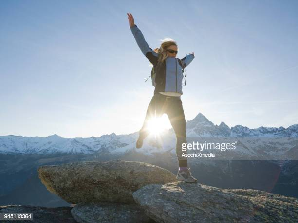 female hiker jumps gap between rocks, mountains below, piedmont, italy - cuneo stock pictures, royalty-free photos & images