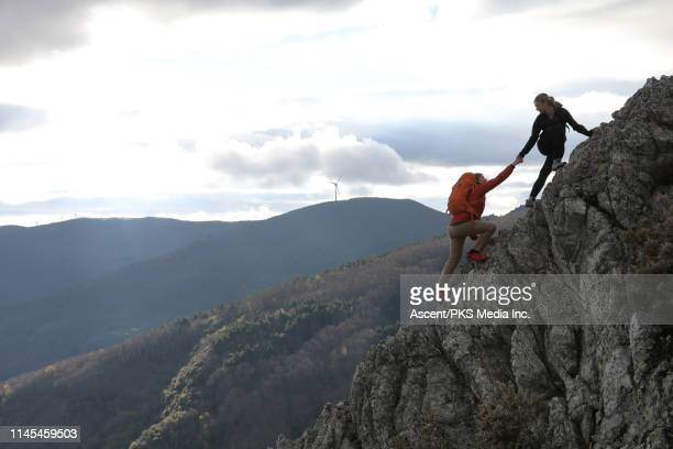 female hiker lends helping hand to male companion - helping hand stock pictures, royalty-free photos & images