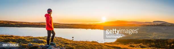Female hiker looking at golden sunrise tranquil mountain lake panorama