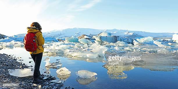 Mujer deportiva mirando a los Icebergs de rayas en la laguna de jökulsárlón Glacial de Islandia
