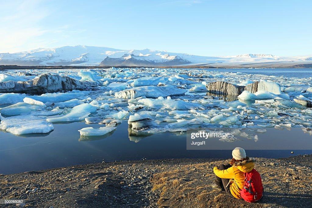 Female Hiker Looking at Icebergs at Jokulsarlon Glacial Lagoon Iceland : Stock Photo