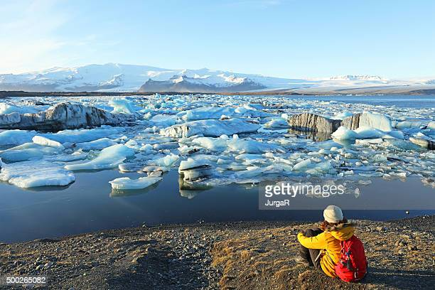 female hiker looking at icebergs at jokulsarlon glacial lagoon iceland - glacier lagoon stock photos and pictures
