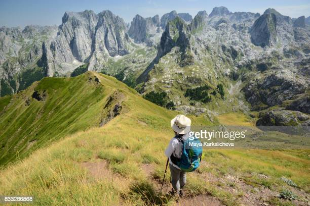 female hiker looking at the beautiful prokletije mountain - montenegro imagens e fotografias de stock