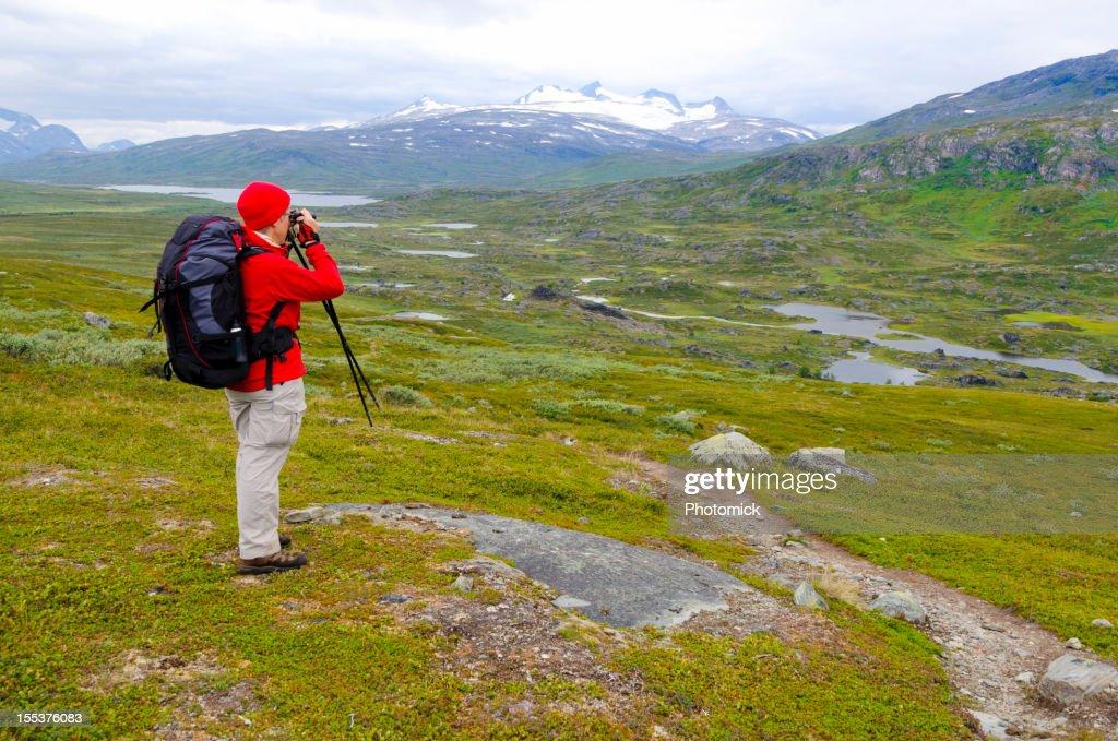 älterer wanderer mit fernglas schaut sich die berge an buy this
