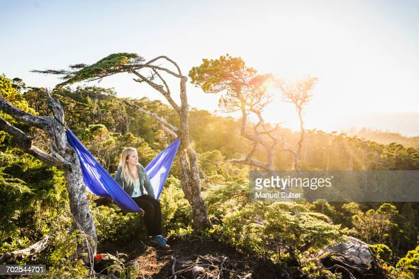Female hiker looking out from hammock, Pacific Rim National Park, Vancouver Island, British Columbia, Canada