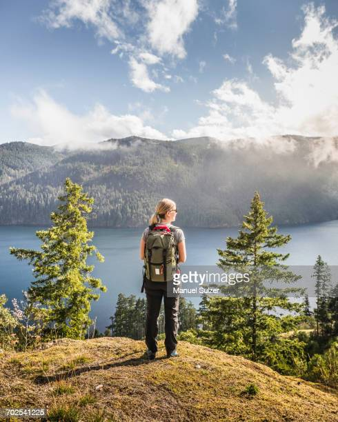 female hiker looking out over comox lake, coutenay, vancouver island, british columbia, canada - stausee stock-fotos und bilder