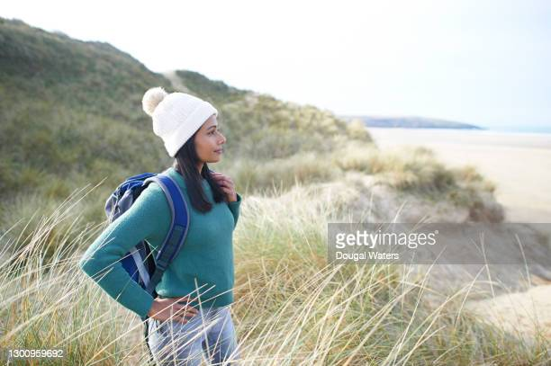 female hiker looking out to sea from sand dunes at beach. - walking stock pictures, royalty-free photos & images