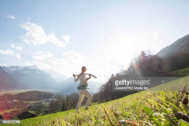 Female hiker looks off from mountain slope, sunrise