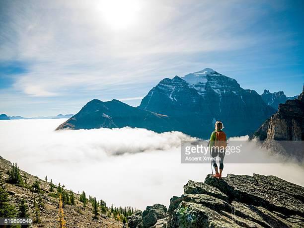 female hiker looks out above fog bank, mtns - en haut photos et images de collection