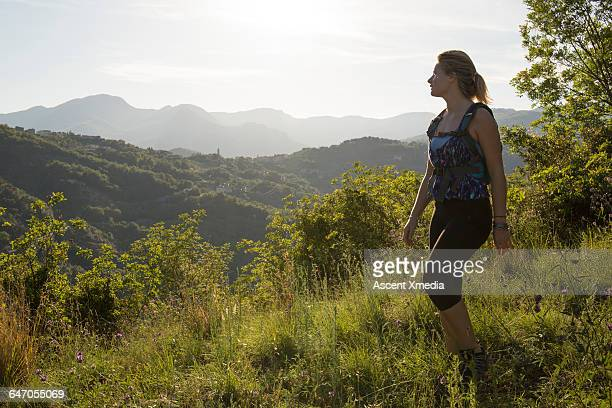Female hiker looks out across hills, from meadow
