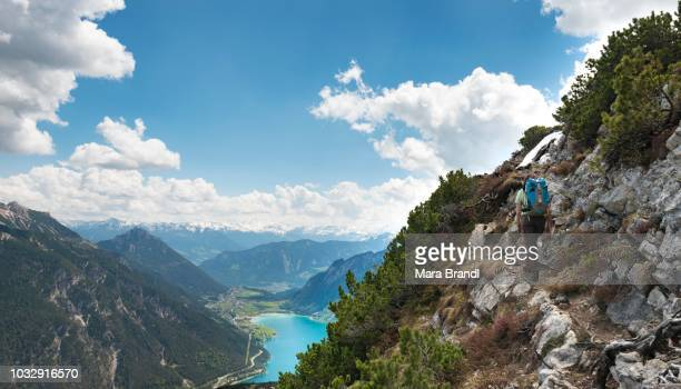 Female hiker on hiking trail, crossing from the Seekarspitz to the Seebergspitz, view of the lake Achensee, Tyrol, Austria