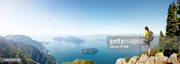 female hiker on top of summit overlooking landscape on sunny day panoramic - canada stock pictures, royalty-free photos & images
