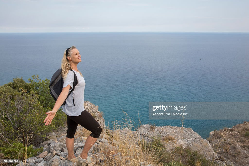 Female hiker opens arms on cliff edge above sea : Stock Photo