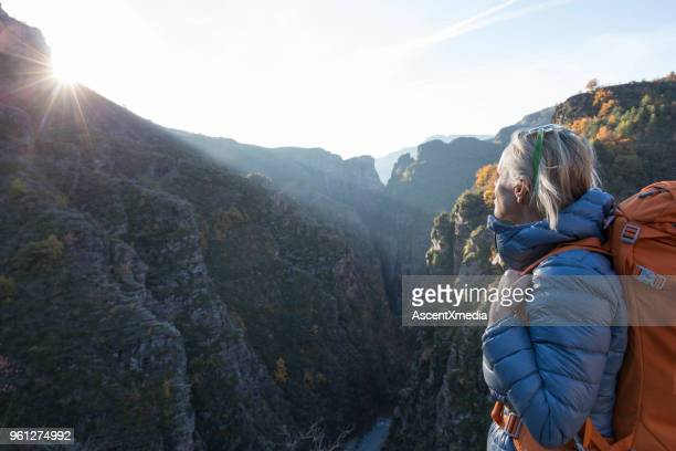 Female hiker pauses above mountain canyon at sunrise