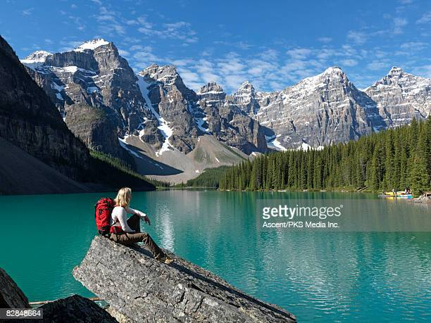 female hiker pauses above shore of moraine lake - moraine lake stock pictures, royalty-free photos & images