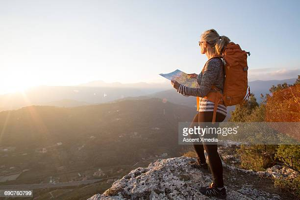 Female hiker pauses to study map, hilly landscape