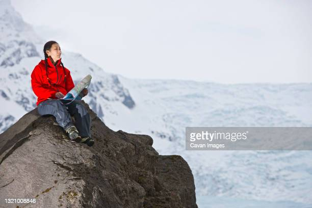 female hiker reading map on rock above glacier - arctic stock pictures, royalty-free photos & images