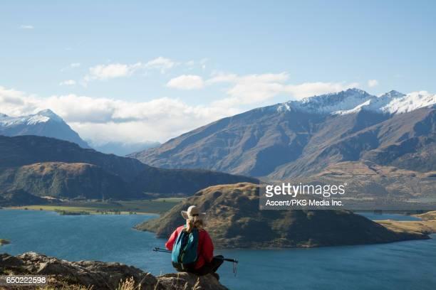 Female hiker relaxes on mountain ridge, above lake