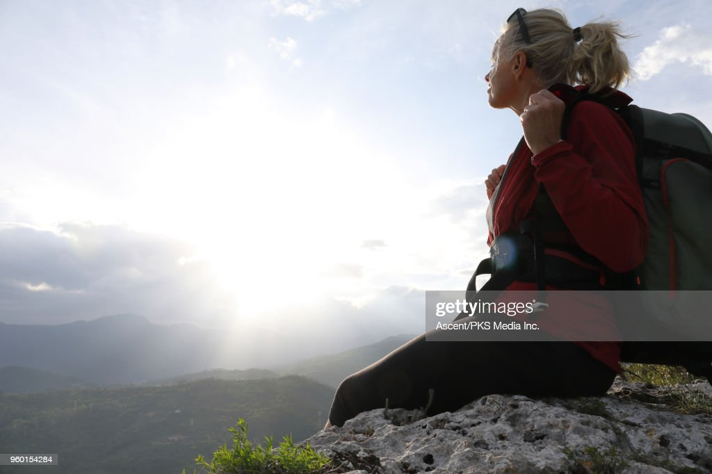 Female hiker relaxes on ridge crest above distant hills : Stock-Foto