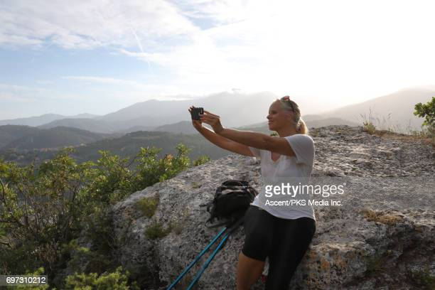 Female hiker relaxes on rock slab above valley, mountains