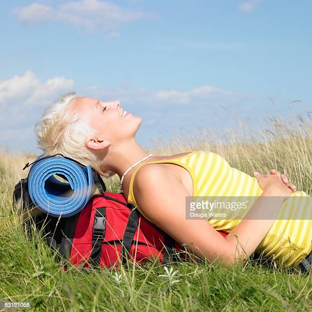 Female hiker resting on rucksack.