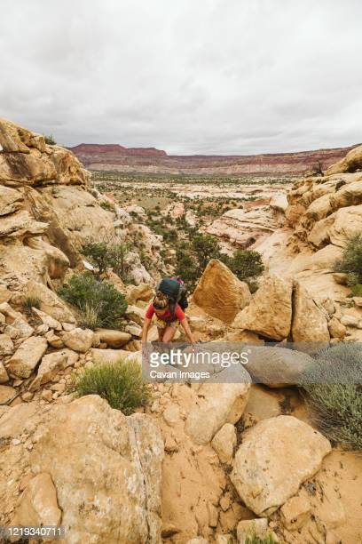 female hiker scrambles up a rock face while hiking in canyonlands utah - スクランブリング ストックフォトと画像