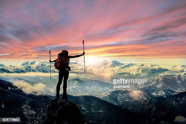 female hiker silhouette at mountain peak - motivation stock pictures, royalty-free photos & images