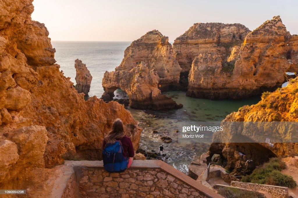 Female hiker sits on stone wall and looks over rocks in the sea, Algarve rocky coast, Ponta da Piedade, Lagos, Portugal : Foto de stock