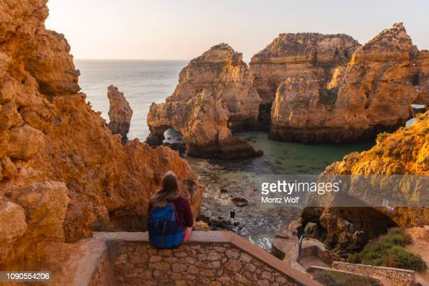 Female hiker sits on stone wall and looks over rocks in the sea, Algarve rocky coast, Ponta da Piedade, Lagos, Portugal