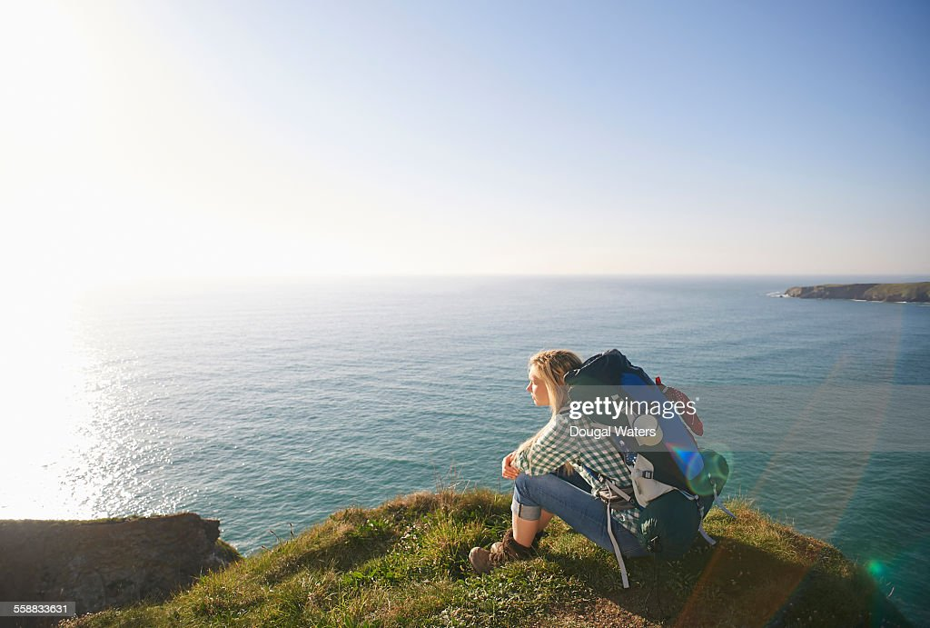 Female hiker sitting atop Atlantic cliff : Stock Photo