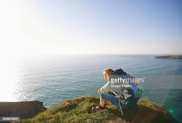 Female hiker sitting atop Atlantic cliff