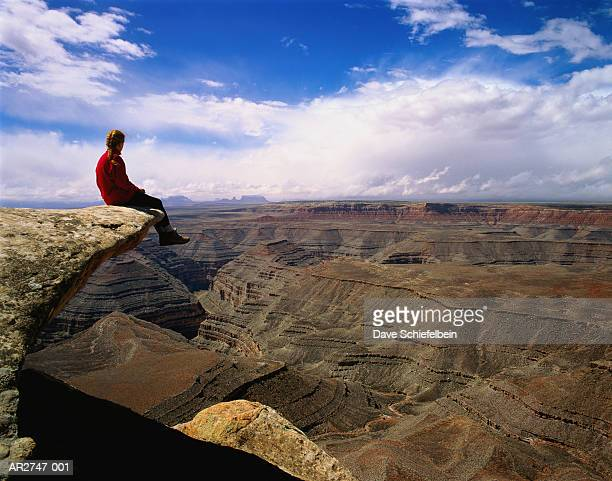 Female hiker sitting on outcrop overlooking canyon, Utah, USA
