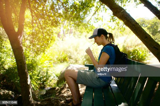 Female hiker sitting to smell a flower