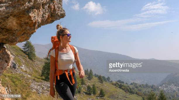 female hiker smiles as she walks along hillside - three quarter length stock pictures, royalty-free photos & images