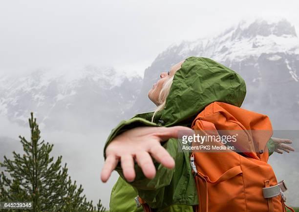 female hiker spreads arms to embrace mountain mist - abenteuer stock-fotos und bilder