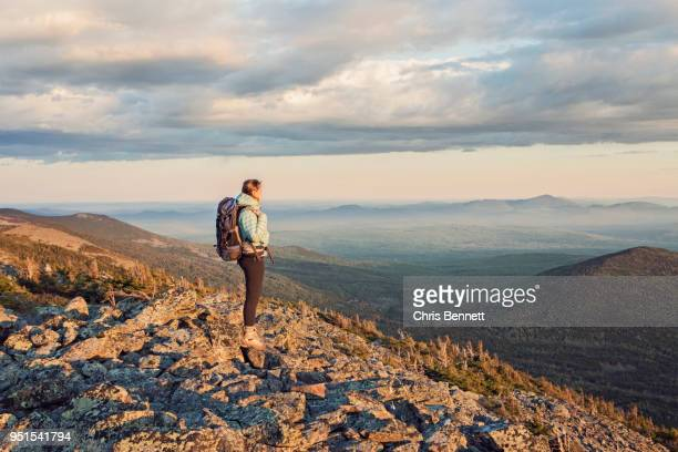 female hiker standing and admiring landscape from top of mount abraham at dusk, maine, usa - appalachian trail stock pictures, royalty-free photos & images