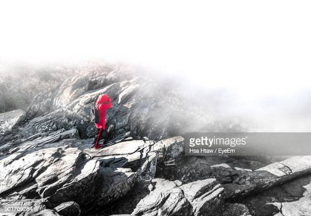 Female Hiker Standing On Mountain During Foggy Weather