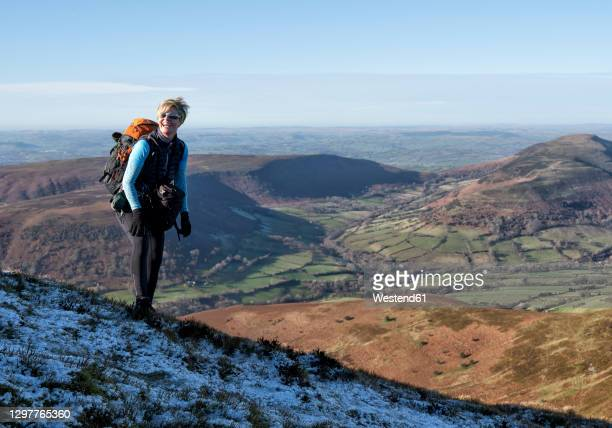 female hiker standing on mountain of crickhowell at brecon beacons, wales, uk - brecon beacons stock pictures, royalty-free photos & images