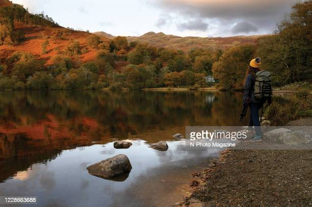 Female hiker standing on the edge of Rydal Water in the Lake District, Cumbria, taken on November 4, 2019.