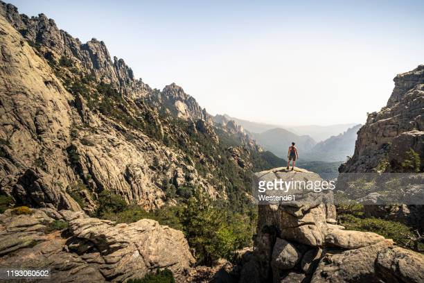 female hiker standing on viewpoint, aiguilles de bavella, corsica, france - corse photos et images de collection