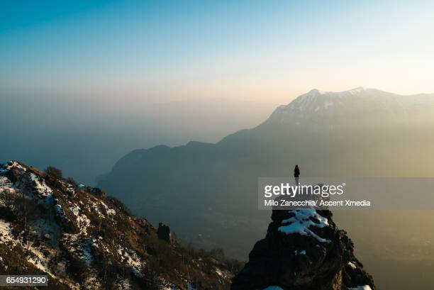 female hiker stands on mountain summit, looks off - finding stock photos and pictures
