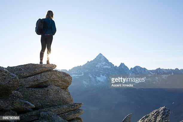 female hiker stands on summit, looks out to mtns - pinnacle stock pictures, royalty-free photos & images