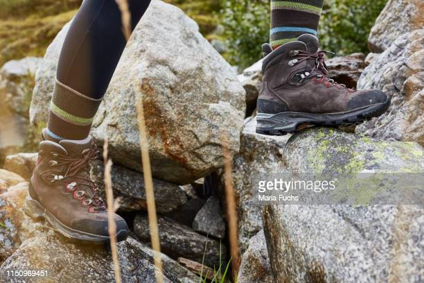 female hiker stepping onto rock, close up of hiking boots - stepping stock pictures, royalty-free photos & images