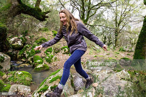 female hiker stepping over woodland boulders, spain - stepping stock pictures, royalty-free photos & images
