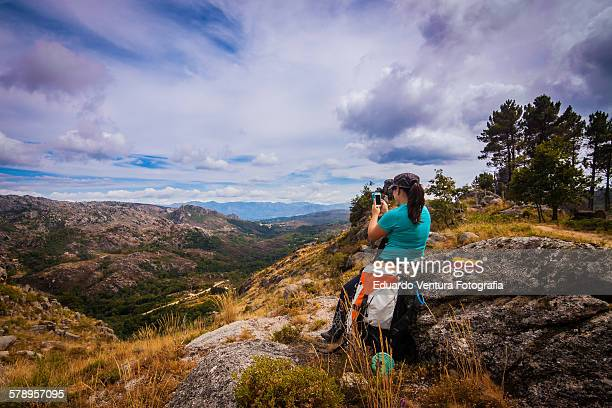 Female hiker takes a picture with her smartphone